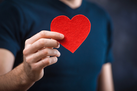 constraining: young bearded man holding red heart made of paper Stock Photo