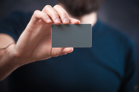 constraining: young bearded man holds a business card, business card template closely
