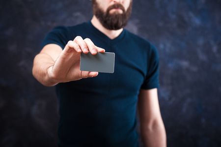 young bearded man holds a business card, business card template