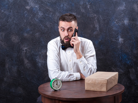constraining: young bearded man surprise talking on the phone Stock Photo