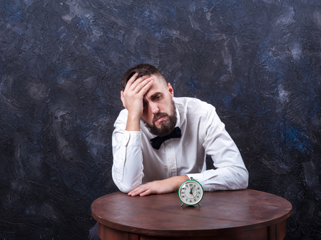 constraining: young bearded man holding his head