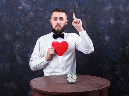 constraining: young bearded man holding red heart and shows thumb up, place for text