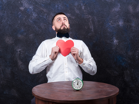 constraining: young bearded man holding a heart, looking up