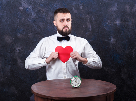 constraining: young bearded man holding a heart and watches, concept for Valentines Day