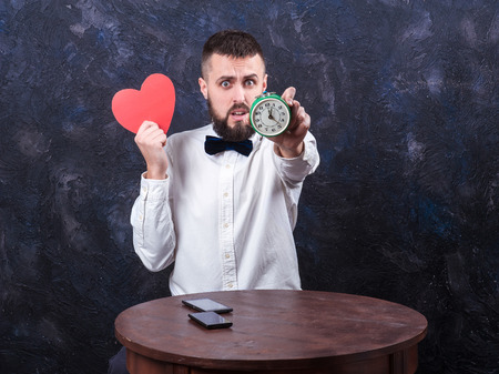 constraining: young bearded man holding a heart and watches, place for an inscription Stock Photo