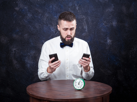 constraining: young bearded man holds hands two phone and looks at his watch, place for an inscription