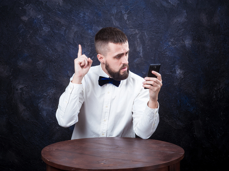 constraining: young bearded man points finger up holding a phone, place for an inscription Stock Photo