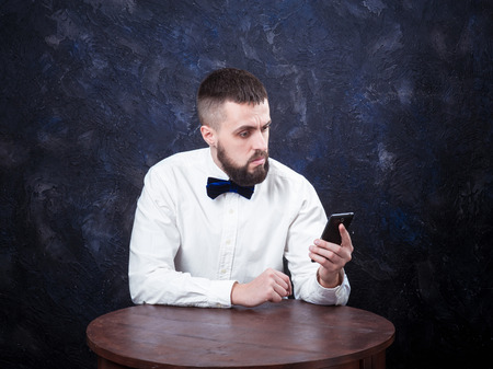 constraining: young bearded man with surprise reads the message in spite of the smartphone, place for an inscription Stock Photo
