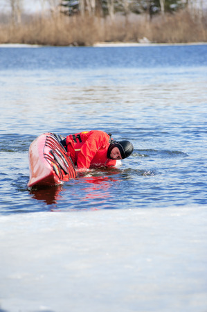athletic man floats on a red boat in calm blue waters river, overturned