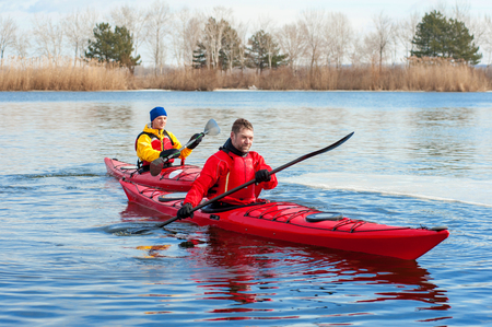 two athletic man floats on a red boat in calm blue waters river