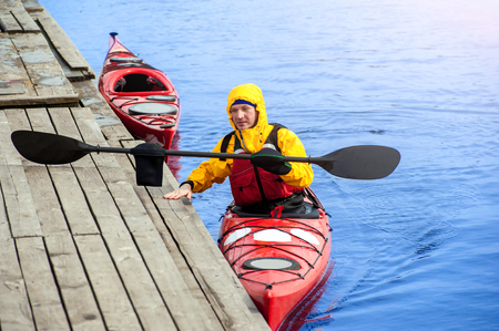 athletic man floats on a red boat in calm blue waters river