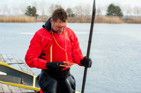 ice floe: sports man kayaking in winter clothes stands on the river bank and writes a message using a smartphone