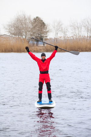standing stone: athletic man stand up paddle board SUP