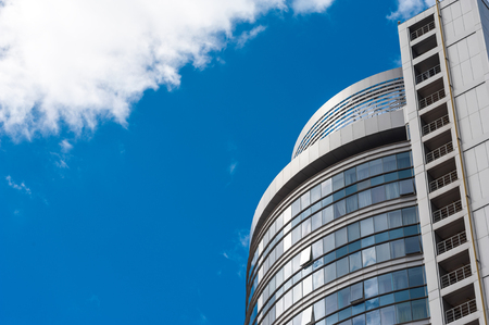 Glass building minimalism of modern architecture and clouds in the blue sky background Stock Photo