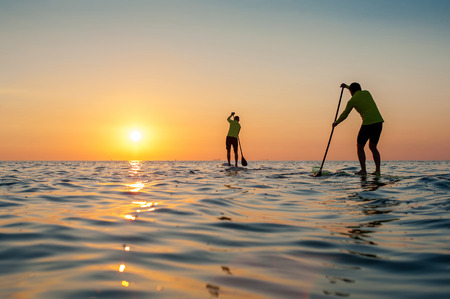 SUP silhouette two man standing with a paddle on the surfboard at sunset stand up paddle boarding, meet the sun