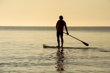 SUP silhouette of athletic man standing with a paddle on the surfboard at sunset stand up paddle boarding Stock Photo