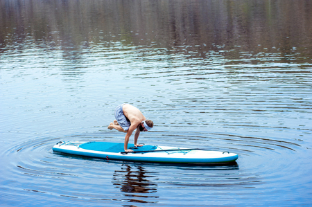 the man is on his hands doing paddle board going paddle boarding