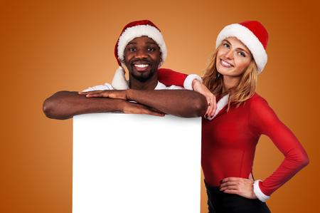 happy christmas couple holding a white board with empty copy space for text Stock Photo