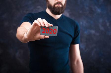 Young bearded man holds a business card with the inscription: 2020