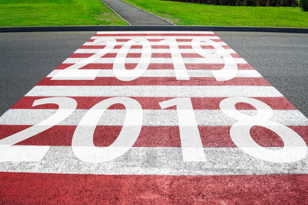 Asphalt road with arrow guideline and 2019 letters painted on the surface. Concept for success in the future goal and passing time. Happy new year