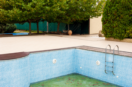 Swimming pool without water in backyard before season opening