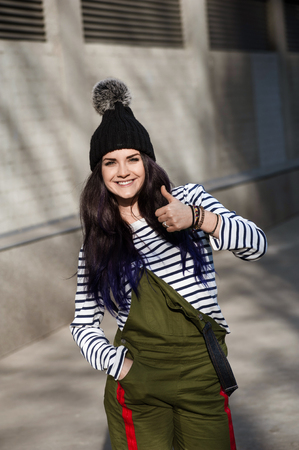 Everything is ok! Beautiful smiling girl showing thumb up gesture. She standing outside in city street and wearing in stripped T-shirt and funny warm hat Banco de Imagens