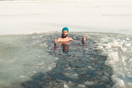 bearded man in hat swimming in the winter lake in the ice hole, ice hole swimming, thumb up Stockfoto