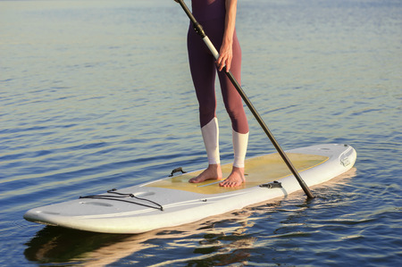 Close up photo. Legs of woman in sportswear standing on stand up paddle board in calm blue river