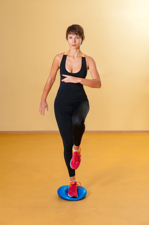 Focused sports woman doing aerobic exercise indoors