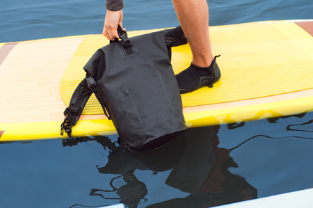 Close up photo. Top view of special bag impervious to water, holded by sports man standing on paddle board on water. Dry bag