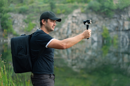 Side view of traveller holding stabilizer for camera while taking photo. He wearing in black T-shirt and baseball cap