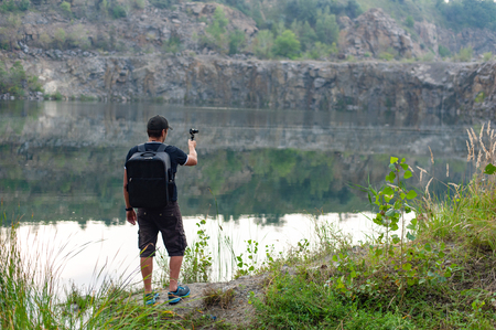 Back view of man taking pictures of beautiful lake on action camera while traveling in wild nature