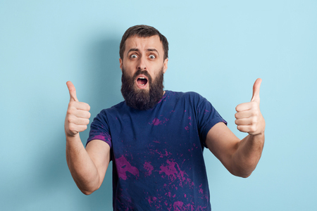 Happy bearded man celebrating being a winner. Dynamic image of caucasian male model on blue studio background. Victory, delight concept. Human facial emotions success concept. Foto de archivo