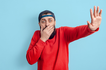 Isolated portrait of guy showing gestures failure with covered mouth and raised another hand with open palm meaning stop sign.