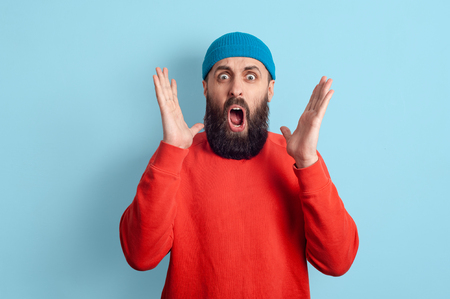 Bearded man learned shocking news. Shocked stupefied man and posing on a blue background. Emotional surprised horrified.