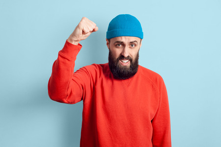 Excited man with fist up. Cheerful hipster guy smiled happily, has excited expression, dressed casually, celebrates his anniversary or promotion at work, isolated over blue studio background.