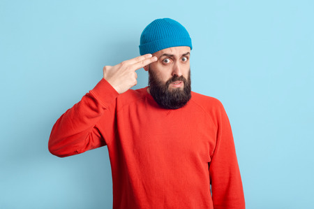Comical male selfishness indoors, shoots at the temple, bows his head, wears hats, a free red sweater, posing on a blue background. Gesture of suicide.