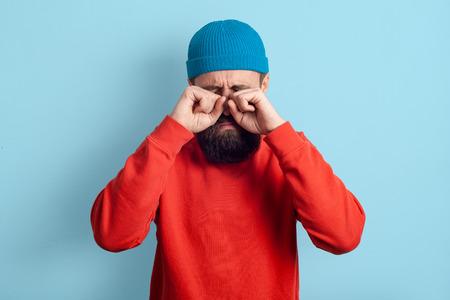 El hombre finge estar llorando. Chico barbudo de pie sobre un fondo azul, las manos se frotaron los ojos. Sentimientos de malestar Foto de archivo
