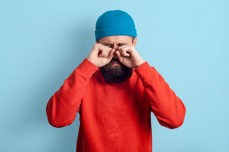 Man pretends to be crying. Bearded guy standing on a blue background, hands rubbed his eyes. Upset feelings
