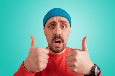 Bliska portret jasnego ekspresyjnego faceta demonstrującego super znak z podniesionymi palcami kciuka na białym tle na turkusowym tle