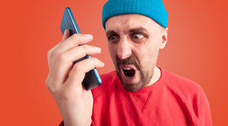 Close up portrait of rude man screaming and swearing at someone with grimace of anger while talking on phone, isolated on red background