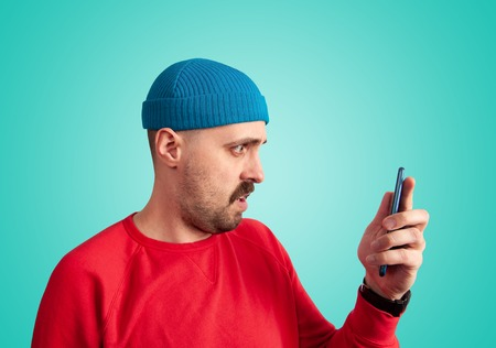 Perplexity facial expression concept. Side view of stylish mustache man in bright clothes holding a phone in front of him and looking at it with disbelief