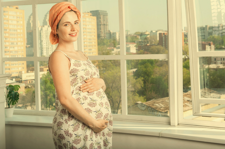 Happy smiling woman while pregnancy at home. She is wearing a romantic sundress and turban and holding her big belly Banque d'images - 125827493