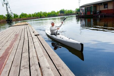 Entertainment on the lake. Low angle photo of man moored to the wooden shore after a boat ride and looking into the camera
