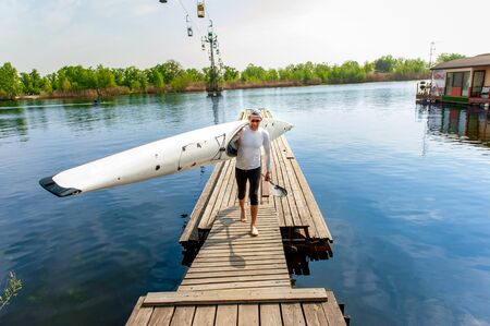 Water leisure in summer. Active young oarsman standing on pier with his equipment, kayak and paddle, after rowing competition Banque d'images