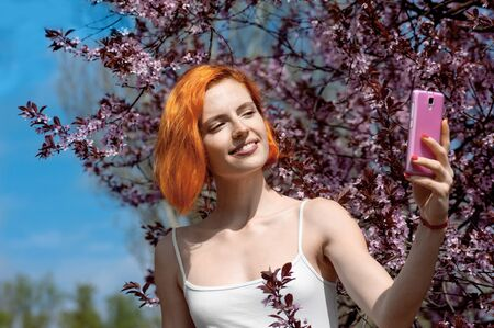 Charming woman with red hair smiling while doing pictures of herself outside in spring season standing against the background of blooming sakura Banque d'images
