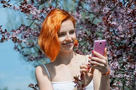 Pretty young girl with red hair in sunlight standing in cherry blossoms garden and using pink modern smartphone Banque d'images - 132823419