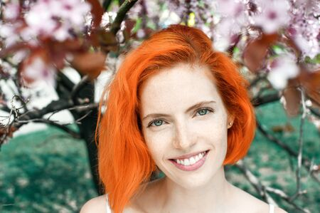 Close up portrait of bright beautyful lady with red hair in blooming park. She smiling and looking at camera with sakura flowers on background Banque d'images