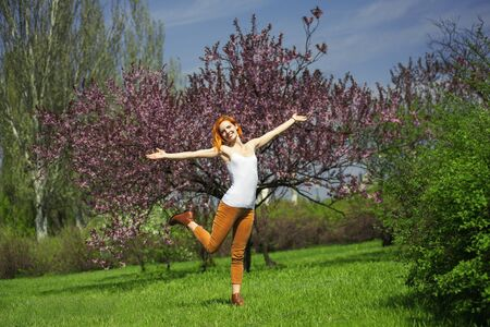 Full length portrait of active adorable girl flying with happiness in spring nature. She smilling and holding raised her arms while standing near wonderful sakura tree Banque d'images
