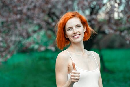Success concept. Charming woman with bright red hair showing thumb up gesture while standing beautiful spring garden with floral trees on background Banque d'images